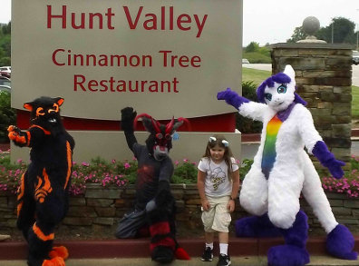 Fursuiters and girl pose in front of a hotel sign