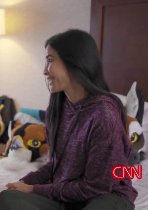 Journalist Lisa Ling sits on a bed, surrounded by fursuit heads.
